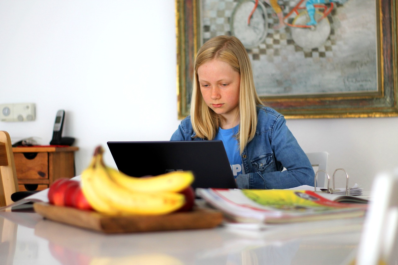A woman sitting at a table using a laptop